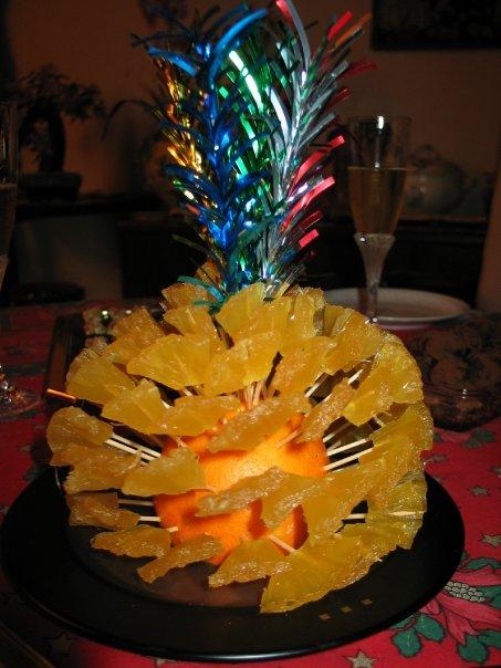 Une orange piquée de morceaux d'ananas confits